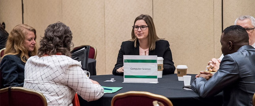 Job seekers chat at a table with NSA representatives about opportunities in computer science at NSA.