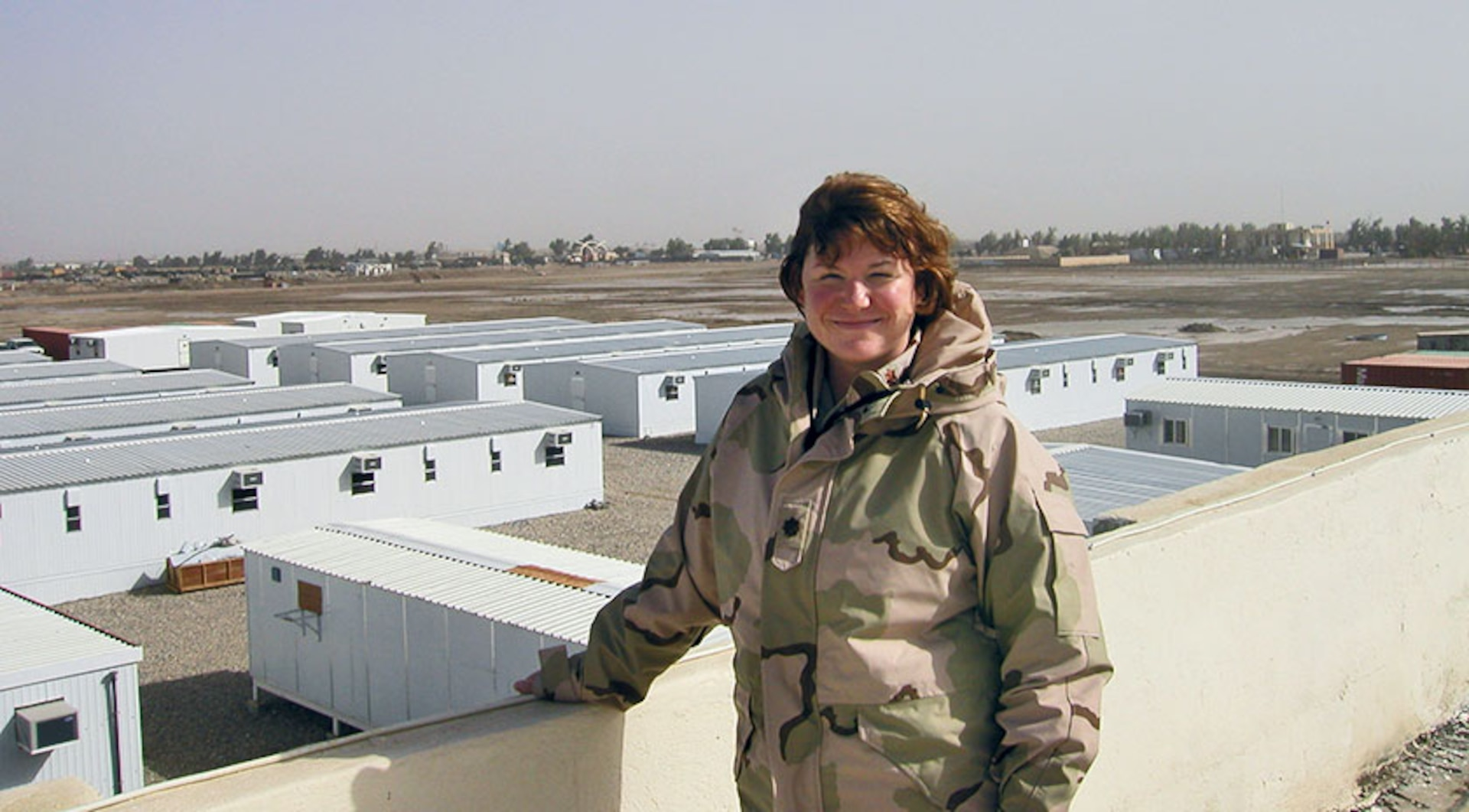 Becky stands on a rooftop overlooking small buildings in a desert town