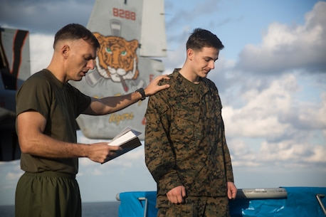 Lt. Cmdr. Jay Weatherwax, the chaplain for the 31st Marine Expeditionary Unit prays for Lance Cpl. Paul Butler, right, a data system administrator with the 31st MEU, during a renewal of faith baptism aboard the flight deck of the amphibious assault ship USS Wasp (LHD 1), underway in the East China Sea, Oct. 21, 2018.