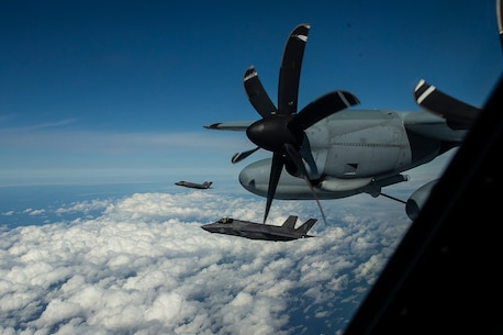 A pair of F-35B Lightning II attack jets fly alongside a KC-130J tanker aircraft during an aerial refueling mission above the East China Sea, Oct. 23, 2018.