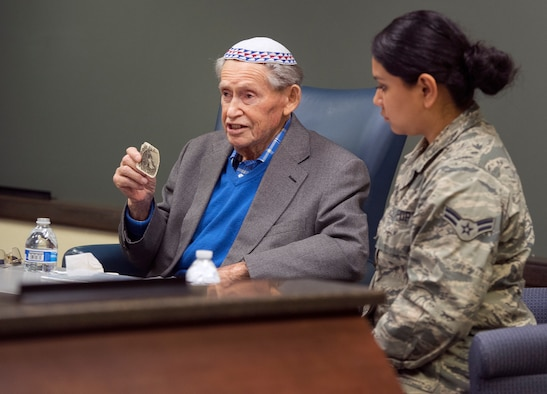 Sam Heider, a Holocaust survivor, holds up a picture of his sister, who was killed by the Nazis, as he talks about his experiences during World War II during a presentation Oct. 19, 2018, at the Air Force Life Cycle Management Center headquarters on Wright-Patterson Air Force Base, Ohio. Heider managed to keep the photo with him and hidden throughout his imprisonment in German concentration camps. It is the only photo he has of any of his family members who all died in the Holocaust. (U.S. Air Force photo by R.J. Oriez)