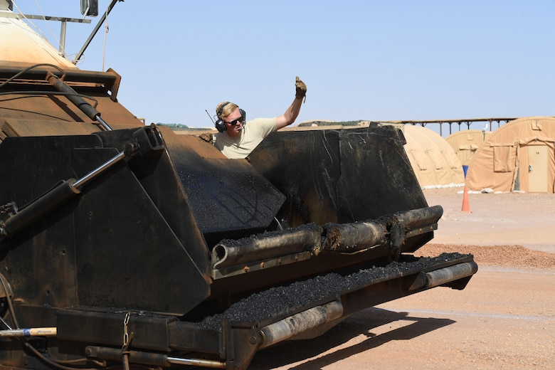 U.S. Air Force Airman 1st Class Conner Roberts, 31st Expeditionary Rapid Engineer Deployable Heavy Operation Repair Squadron Engineer pavement and equipment journeyman, signals to the dump truck to start loading the Material Transfer Vehicle with asphalt at Nigerien Air Base 201, Agadez, Niger, Oct. 19, 2018. The MTV allows Airmen to pave continuously with well-mixed asphalt. (U.S. Air Force photo by Tech. Sgt. Rachelle Coleman)