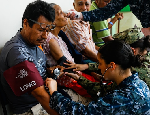 A U.S. Navy Hospitalman checks the blood pressure of a patient in Ecuador.