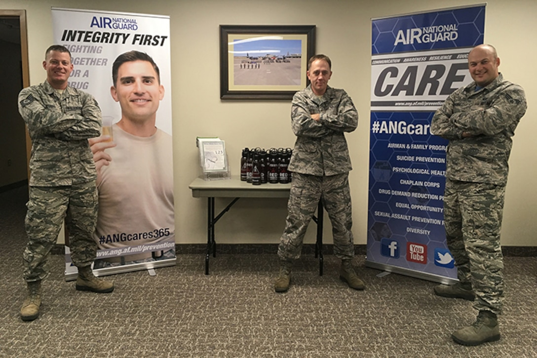 Air National Guard personnel pose in front of banners made for Red Ribbon Week.