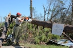 U.S. Air Force Staff Sgt. Colleen Curren, a structures journeyman with the 202nd Rapid Engineer Deployable Heavy Operational Repair Squadron Engineers (RED HORSE) , chainsaws through a fallen tree on Debi Road in the Bayou George area of Panama City, Florida, Oct. 14, 2018, after Hurricane Michael. (U.S. Air National Guard photo by Staff Sgt. Carlynne DeVine)