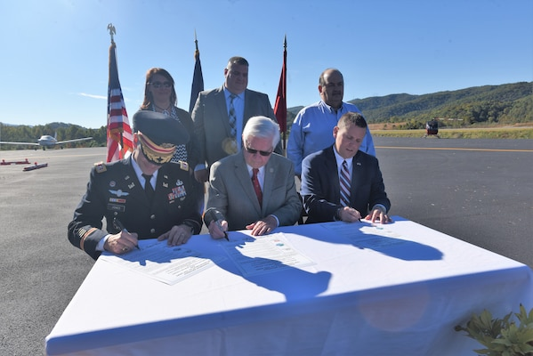(Front Row, Left to Right) Lt. Col. Cullen Jones, Nashville District commander; U.S. Rep. Hal Rogers, representing Kentucky's 5th Congressional District, and Dan Mosley, Harlan County Judge Executive, sign a partnership agreement at Tucker Guthrie Memorial Airport Oct. 18, 2018 to formally announce the extension of sewer services to 50 residences and 20 commercial structures along Airport Road. (USACE photo by Lee Roberts)