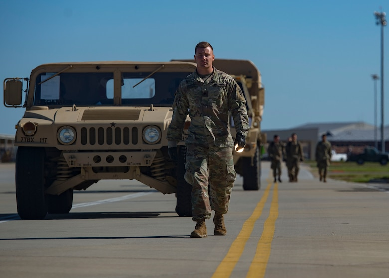 U.S. Army Spc. Brett Tessnear, 119th Inland Cargo Transfer Company, 11th Transportation Battalion, 7th Transportation Brigade (Expeditionary) motor transport operator, leads vehicles on the flight line during a training exercise at Joint Base Langley-Eustis, Virginia, Oct. 18, 2018.