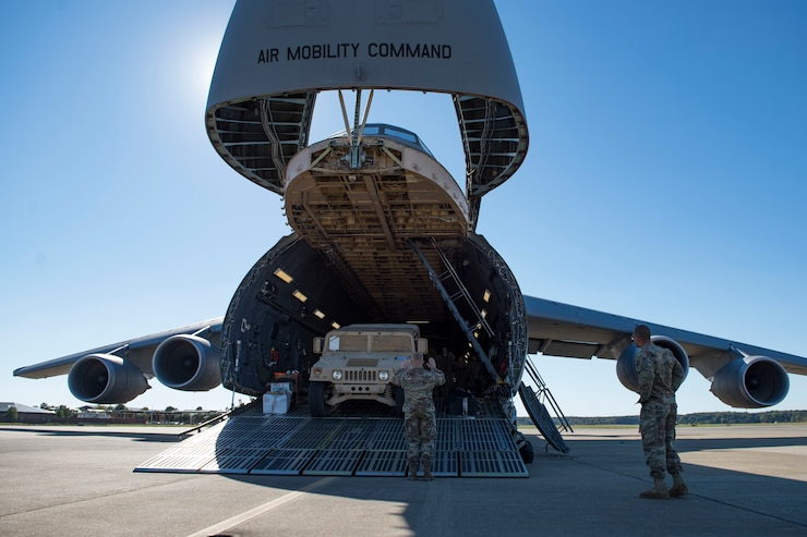 U.S. Army Soldiers assigned to the 119th Inland Cargo Transfer Company, 11th Transportation Battalion, 7th Transportation Brigade (Expeditionary) guide vehicles onto a U.S. Air Force C-5M Super Galaxy during a training exercise at Joint Base Langley-Eustis, Virginia, Oct. 18, 2018.