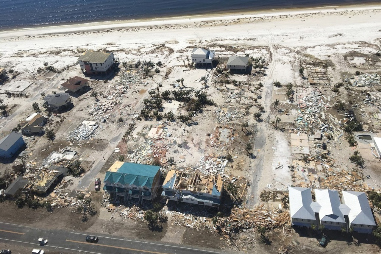 An aerial view shows devastated buildings along a sandy coast.