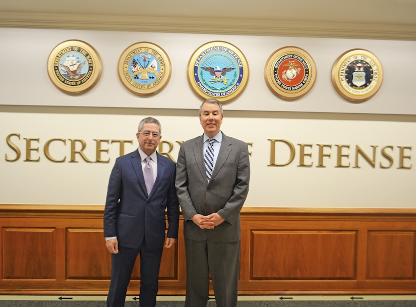 Two men in suits pose for a photo with military seals in the background.