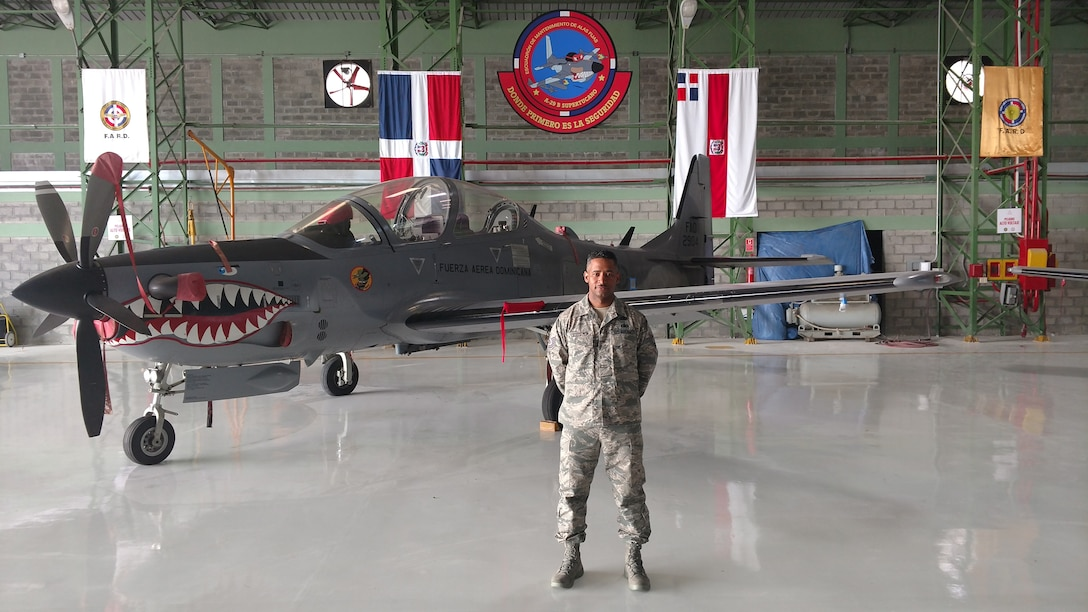 Tech. Sgt. Rafael Escoto Roa, 571st Mobility Support Advisory Squadron air transportation specialist air advisor, poses in-front of an A-29 Super Tucano aircraft, at the San Isidro Air Base in Santo Domingo, Dominican Republic. (Courtesy Photo)