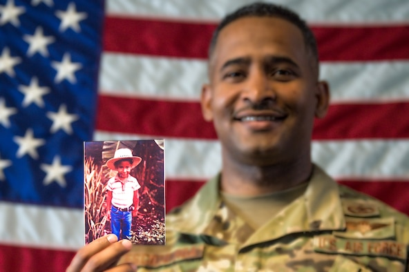 Tech. Sgt. Rafael Escoto Roa, 571st Mobility Support Advisory Squadron air transportation specialist air advisor, holds a picture of himself as a child, as he tells the story of his life in the Dominican Republic and how he moved to the United States in pursuit of the American dream. (U.S. Air Force photo by Tech. Sgt. Liliana Moreno)