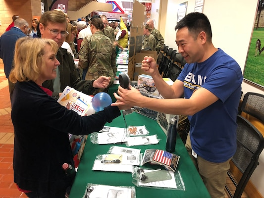 A Brooke Army Medical Center staff member tests the grip strength of an attendee during the Joint Base San Antonio and Brooke Army Medical Center Military Retiree Appreciation Day Oct. 20 in the hospital's Medical Mall.