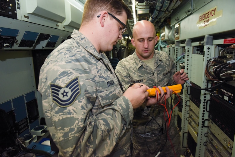 U.S. Air Force Tech. Sgt. Brett Edholm, 95th Reconnaissance Squadron, electrical warfare systems NCO- in-charge, and Staff Sgt. Randy Duncan, 95th RS RC-135 Rivet Joint electronic warfare craftsman, check the voltage on loose fiber optic cables on a RC-135 Rivet Joint at RAF Mildenhall, England, Oct. 16, 2018.