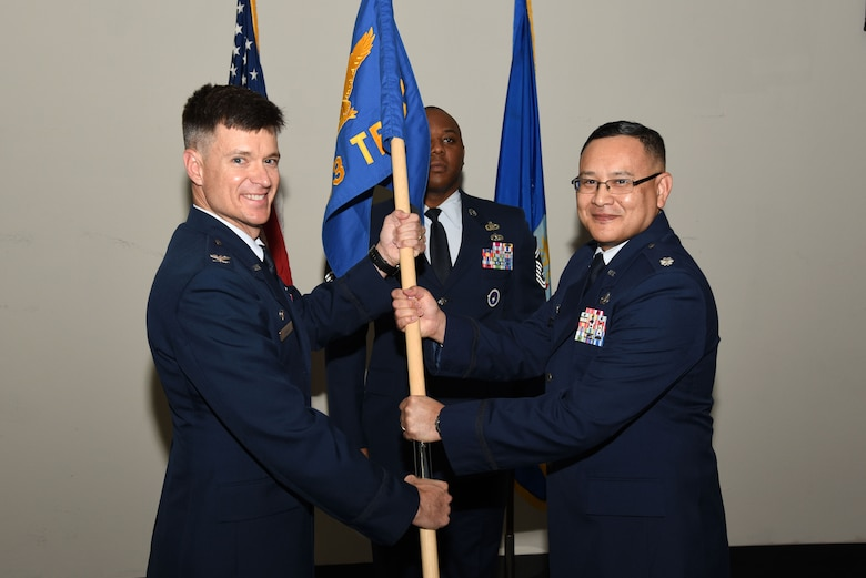 U.S. Air Force Col. Thomas Coakley, 17th Training Group commander, passes the 313th Training Squadron guideon to Lt. Col. David Sarabia, 313th TRS commander, during the 313th TRS Assumption of Command at the Event Center on Goodfellow Air Force Base, Texas, Oct. 24, 2018. As the 313th TRS commander, Sarabia is responsible for providing world-class international, mission-qualification, as well as intermediate and advanced intelligence, surveillance and reconnaissance training to develop and inspire professionals for the Department of Defense and our international partners. (U.S. Air Force photo by Staff Sgt. Joshua Edwards/Released)