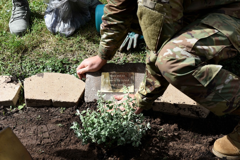 U.S. Air Force Staff Sgt. Dillon Duermyer, 17th Medical Support Squadron medical records NCO in charge, lays a memorial plaque near Leftwich Hall on Goodfellow Air Force Base, Texas, Oct. 23, 2018. Goodfellow dedicated a pavilion along the troop walk as a second memorial to Tech. Sgt. Raymond Leftwich. (U.S. Air Force photo by Senior Airman Randall Moose/Released)