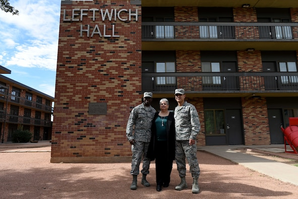 U.S. Air Force Chief Master Sgt. Lavor Kirkpatrick, 17th Training Wing command chief, 17th Medical Group Admin Support Rhonda Leftwich, and Col. Ricky Mills, 17th TRW commander, stand near Leftwich Hall on Goodfellow Air Force Base, Texas, Oct, 23, 2018. Goodfellow honored Tech. Sgt. Raymond Leftwich at the Taylor Chapel and outside the building that bears his name. (U.S. Air Force photo by Senior Airman Randall Moose/Released)