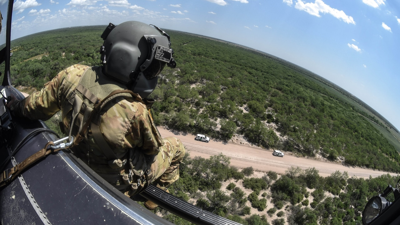 A soldier looks out from an aircraft onto two vehicles on a roadway.