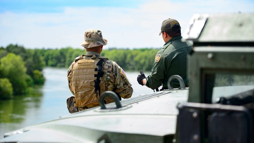 A service member and a border patrol agent, shown from behind, talk while standing by a river.