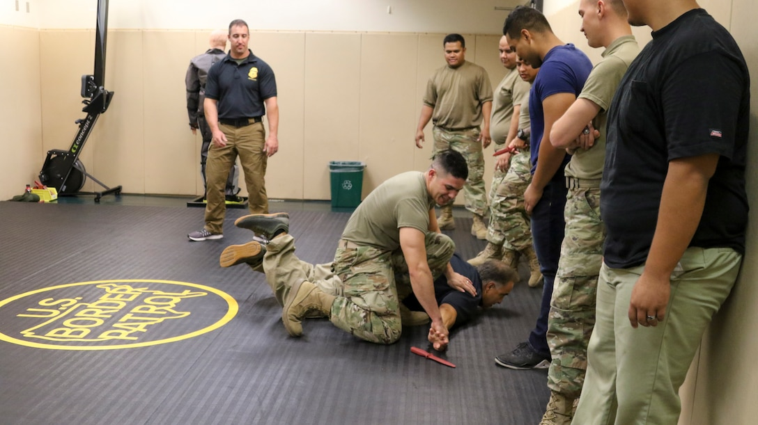 A guardsman wrestles with an instructor in a gym as other troops watch.