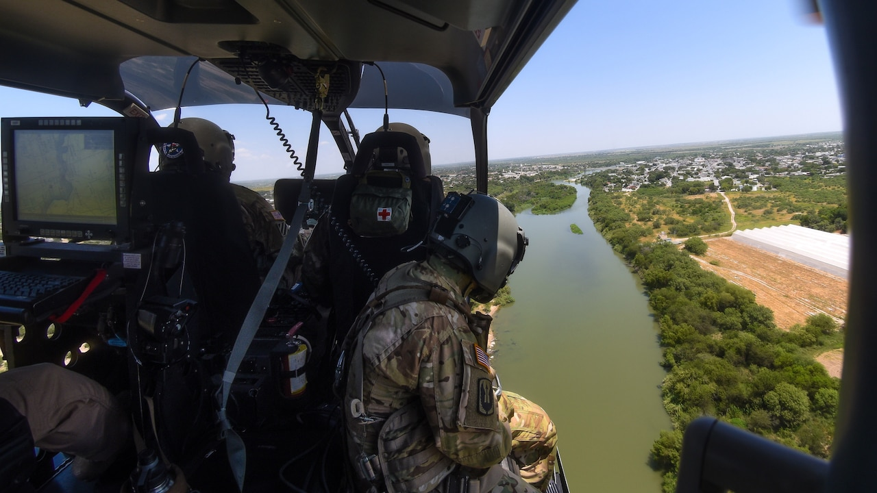 Guardsmen in an aircraft fly over a river.