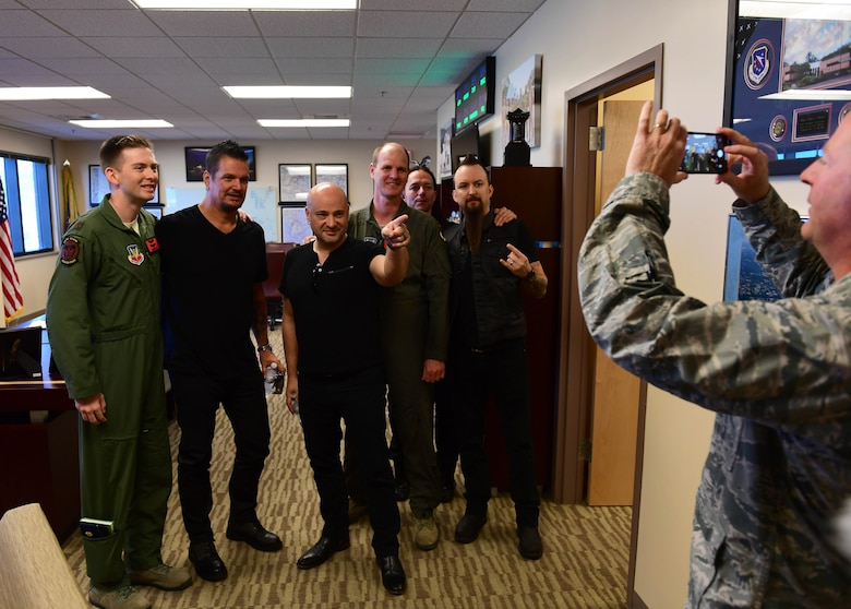 Disturbed band members take a photo with 432nd Wing/432nd Expeditionary Wing pilots in wing headquarters at Creech Air Force Base, Nevada, Oct. 23, 2018. Disturbed came to Creech via the USO and performed a concert for Airmen after learning about the wing mission. (U.S. Air Force photo by Senior Airman Christian Clausen)