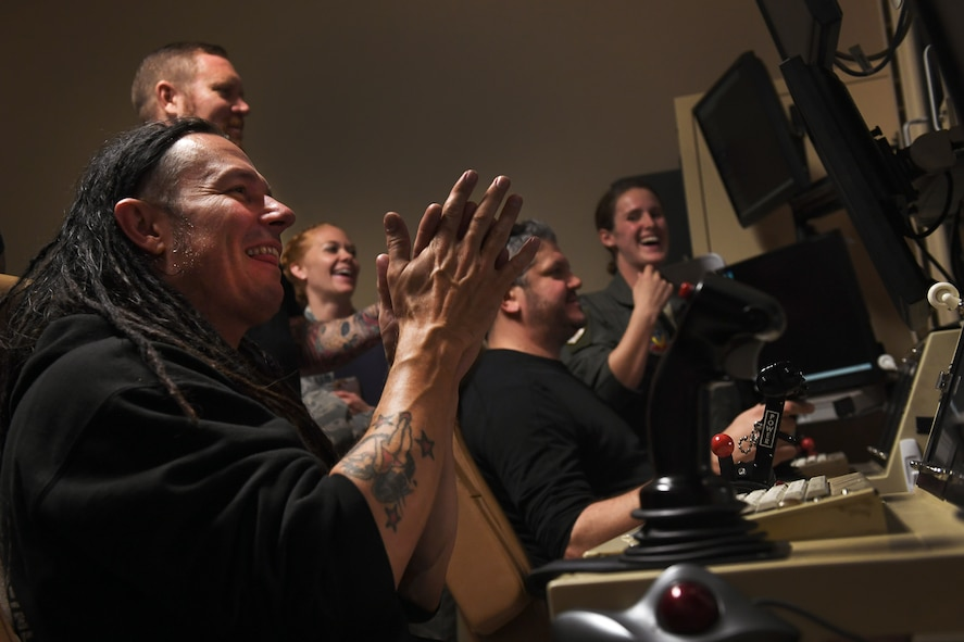 John Moyer, Disturbed bassist, shares a laugh with Creech Airmen during a simulator mission at Creech Air Force Base, Nevada Oct. 23, 2018. Disturbed partnered with the USO to perform a concert for Creech Airmen after learning about the wing mission. (U.S. Air Force photo by James Thompson)