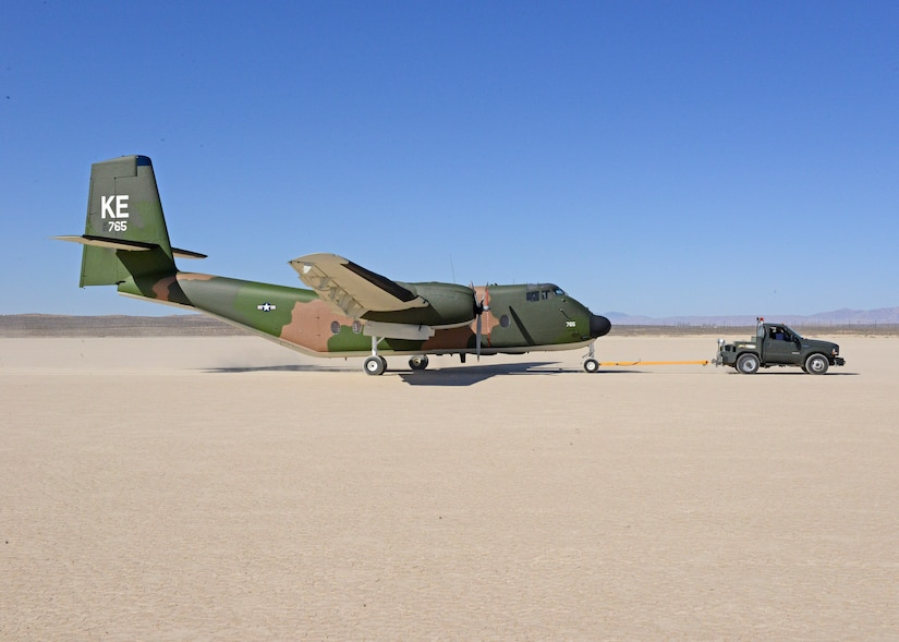 A C-7A Caribou is towed across Rogers Dry Lakebed from Edwards AFB's main base to the Air Force Flight Test Museum restoration hangar Oct. 15. (U.S. Air Force photo by Kenji Thuloweit)