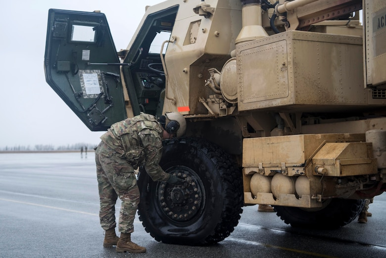U.S. Army Pfc. Mary Slatten, a High Mobility Artillery Rocket System (HIMARS) driver, assigned to Alpha Battery, 3rd Battalion, 27th Field Artillery Regiment (HIMARS), 18th Field Artillery Brigade, Fort Bragg, N.C., deflates the tires of a M142 HIMARS at Fort Greely, Alaska, Oct. 19, 2018, during Red Flag-Alaska 19-1. Slatten's unit was tasked to provide long-range artillery support during RF-A, allowing the unit to showcase its capabilities and develop relationships with other services. Transporting the M142 HIMARS in a U.S. Air Force C-130J Super Hercules requires deflating the tires and lowering the suspension.