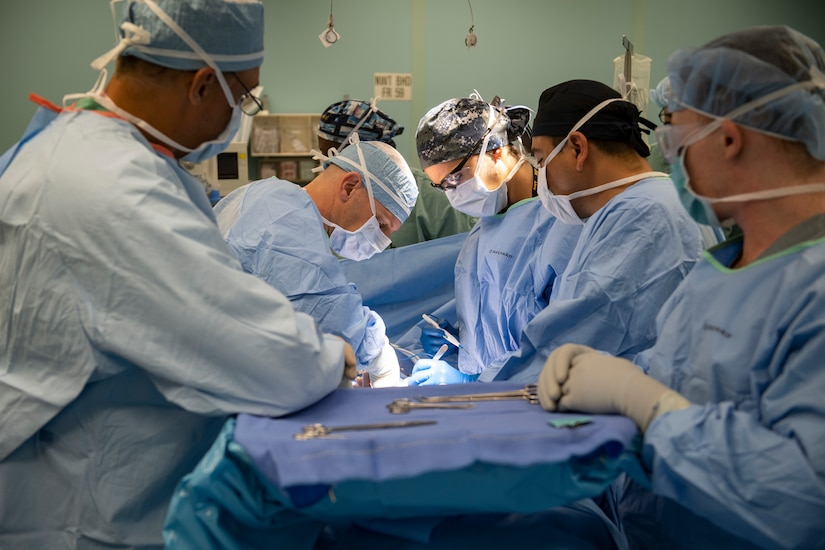 A surgical team works on a patient.