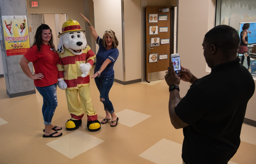 "U.S. Air Force Tech. Sgt. Marshall Boykins, 18th Civil Engineer Squadron NCO in-charge of fire inspections, takes a photo of Lacey Holmstrom, left, Parent Teacher Organization vice president, Sparky the Fire Dog and Jennifer Fountain, PTO president, Oct. 10, 2018, at Kadena Elementry School on Kadena Air Base, Japan. This year's campaign for Fire Prevention Week is ""Look. Listen. Learn. Be aware, fire can happen anywhere."" The campaign focuses on educating people about how they can reduce the likelihood of having a fire and how to escape safely during a fire. (U.S. Air Force photo by Staff Sgt. Micaiah Anthony)"