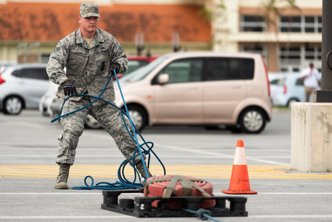 U.S. Air Force Senior Airman Forrest Privette, 18th Civil Engineer Squadron firefighter, pulls a sled during the 2018 Fire Muster Oct. 11, 2018, at Kadena Air Base, Japan.  A fire muster gives people a chance to experience tasks a firefighter would during an emergency. (U.S. Air Force photo by Airman 1st Class Matthew Seefeldt)