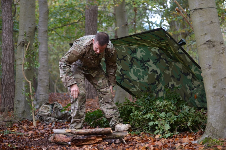 Tech. Sgt. Dereck Day, a 48th Operations Support Squadron Survival, Evasion, Resistance and Escape specialist, demonstrates how to build a reliable shelter at Royal Air Force Lakenheath, England, Oct. 18, 2018. Participants of the one-day SERE training were asked to build shelters from both natural and man-made resources to test their survival skills. (U.S. Air Force photo by Airman 1st Class Shanice Williams-Jones)