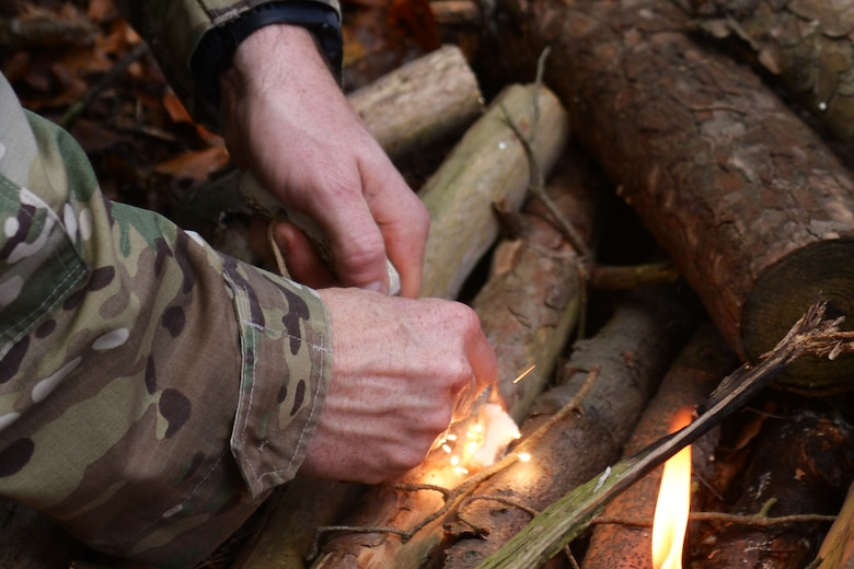 Tech. Sgt. Dereck Day, a 48th Operations Support Squadron Survival, Evasion, Resistance and Escape specialist, demonstrates how to start a fire during SERE training at Royal Air Force Lakenheath, England, Oct. 18, 2018. SERE training participants learned how to build and use both warmth and signal fires. (U.S. Air Force photo by Airman 1st Class Shanice Williams-Jones)
