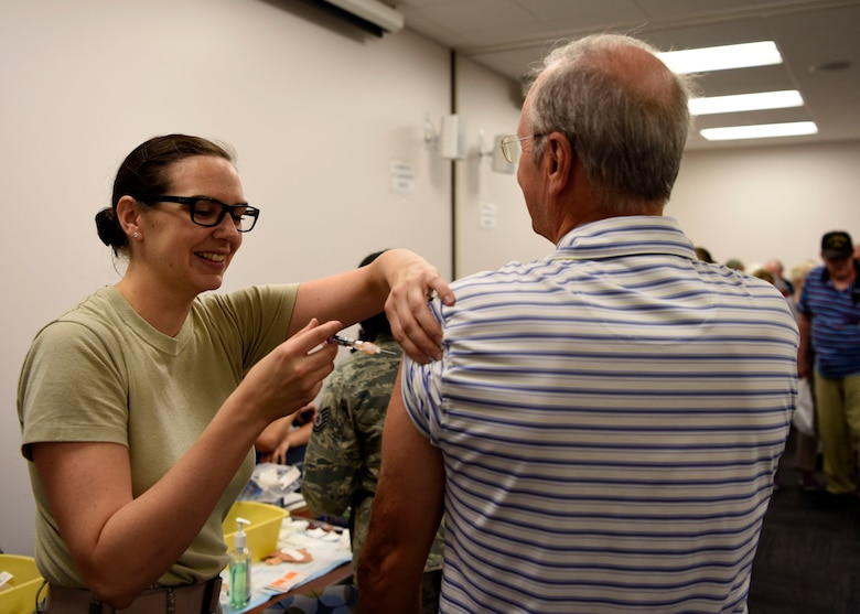 An Airman assigned to the 56th Medical Group administers a shot to a veteran during Retiree Appreciation Day event Oct. 20, 2018, at Luke Air Force Base, Ariz.