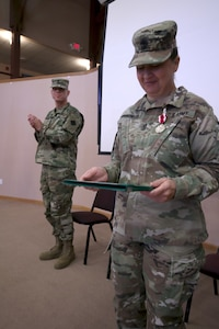 Command Sgt. Maj. Sara E. Noskowiak, outgoing U.S. Army Reserve Music Sergeant Major, 88th Readiness Division, smiles proudly at her Meritorious Service Medal, given to her by Maj. Gen. Patrick J. Reinert, 88th Readiness Division commanding general, during the U.S. Army Reserve Music change of responsibility ceremony at Fort McCoy, Wisconsin, October 20, 2018. Her successor, Master Sgt. Keith M. Barlow, applauds behind her. Noskowiak helped bring the position of U.S. Army Reserve Music Sergeant Major to the attention of U.S. Army Reserve Command by having all the readiness divisions sign a memorandum agreeing to support the position which manages all of the U.S. Army Reserve Music units.