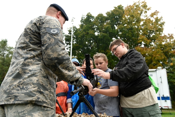 Casey Reed and Uriah Blair, Boy Scouts from Troop 304 out of Findlay, Ohio, learns about the different weapons from Staff Sgt. Kyle York, a security forces specialist assigned to the 180th Fighter Wing, Ohio Air National guard during the Camp Frontier  50th Anniversary camporall Oct. 6, 2018 in Pioneer, Ohio. Airmen from the 180FW participated in the event, helping to build and sustain the relationship with the Northwest Ohio community. (U.S. Air National Guard Photo by Staff Sgt. Shane Hughes)