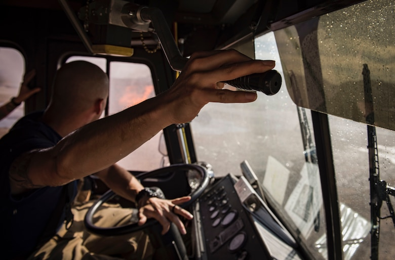 Airman 1st Class Matthew Trevizo, 99th Civil Engineer Squadron firefighter, maneuvers a water cannon on his fire truck towards a simulated aircraft fire during a training exercise Oct. 23, 2018, at Nellis Air Force Base, Nev. Trevizo was also responsible for driving the truck at the same time he operated the water cannon. (U.S. Air Force photo by Airman 1st Class Andrew D. Sarver)