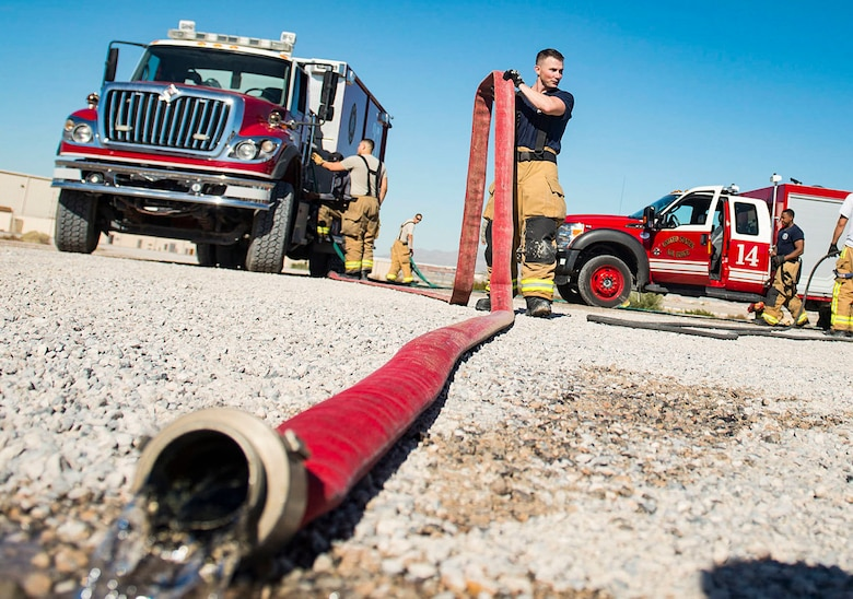 Staff Sgt. Edward Wooten, 99th Civil Engineer Squadron firefighter, prepares to roll up a fire hose at the fire department training area on Nellis Air Force Base, Nev., Oct 24, 2018. Primarily Nellis/Creech fire departments participate in the annual training together, but local fire departments from around Las Vegas may also participate. (U.S. Air Force photo by Airman 1st Class Bryan T. Guthrie)