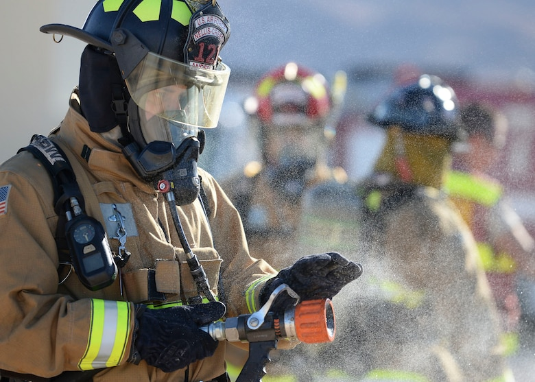 Lt. Andrew Anderson, 99th Civil Engineer firefighter, tests his fire hose during an exterior rear aircraft training at the fire department training area on Nellis Air Force Base, Nev. Oct 22, 2018. Airport and rescue fire fighting vehicles are designed to disperse around 2,000 gallons per minute. (U.S. Air Force photo by Airman 1st Class Bryan T. Guthrie)