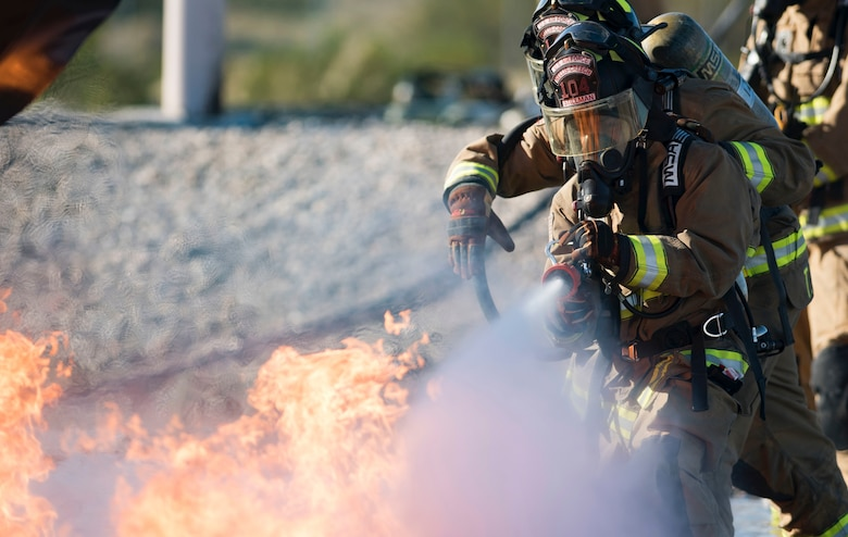Airman 1st Class Christopher Stillman, 99th Civil Engineer Squadron firefighter, uses a hose to put out a fire during a training exercise Oct. 23, 2018, at Nellis Air Force Base, Nevada. The training exercise simulated a crashed plane and gave the firefighters an opportunity to practice fighting aircraft fires. (U.S. Air Force photo by Airman 1st Class Andrew D. Sarver)