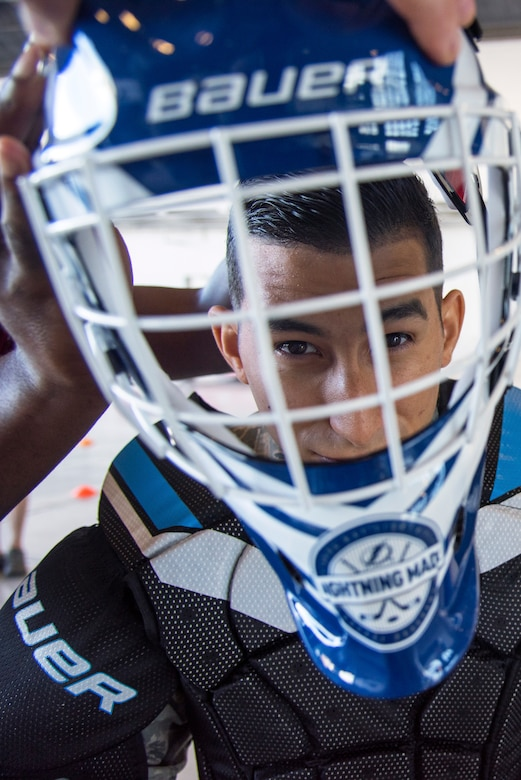 U.S. Air Force Airman 1st Class Caleb Nunez, a photojournalist assigned to the 6th Air Mobility Wing, puts on a hockey helmet at MacDill Air Force Base, Florida, Oct. 25, 2018.
