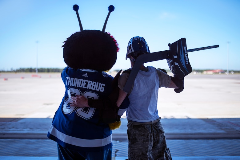 The Tampa Bay Lightning team mascot, the ThunderBug, looks over the flight line with an Airman at MacDill Air Force Base, Florida, Oct. 25, 2018.