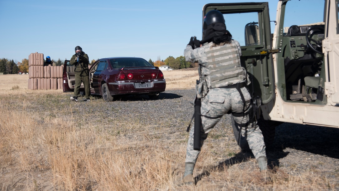 Airman 1st Class Tonya Brackens, 92nd Security Forces Squadron installation entry controller, simulates returning fire to an aggressive role-player during a high-risk situation training exercise at Fairchild Air Force Base, Washington, Oct. 15, 2018. Trainees practiced entry controller, traffic stops and domestic situations during which they didn't know what they might encounter. Training how to approach an unknown situation is a vital skill Defenders have to learn to remain as safe as possible. (U.S. Air Force photo/ Senior Airman Ryan Lackey)