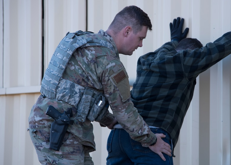 U.S. Air Force Staff Sgt. Jordan Regan, 92nd Security Forces Squadron installation patrolman, frisks a role-player during a high-risk situation training exercise at Fairchild Air Force Base, Washington, Oct. 15, 2018. SFS Airmen are a base's police force, acting as both front-line defense from outside attack and keepers of the peace for base residents. (U.S. Air Force photo/Senior Airman Ryan Lackey)