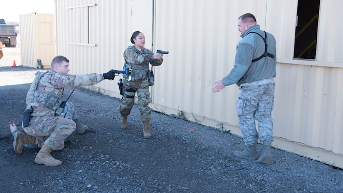 Airmen from the 92nd Security Forces Squadron simulate facing-off against an armed role-player during a high-risk situation training exercise at Fairchild Air Force Base, Washington, Oct. 15, 2018. The training scenarios mirrored past events Security Forces Airmen and civilian police forces alike have encountered at both deployed and domestic locations, so instructors already know what has worked in before to prepare their Airmen should it happen again. (U.S. Air Force photo/ Senior Airman Ryan Lackey)