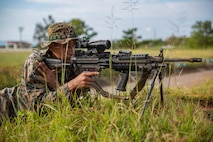 Cpl. Levi Galindo sights in on a target with a M249 Light Machine Gun during a fire and movement range Oct. 24, 2018, at Camp Hansen, Okinawa, Japan. During the range, Marines with 3rd Marine Logistics Group practiced their marksmanship skills, improved their communication and worked on their weapons handling while engaging targets. Galindo is a native of Las Vegas, Nevada, and is a machine gunner with the Tactical Readiness and Training, G-3, 3rd Marine Logistics Group Headquarters. (U.S. Marine Corps photo by Lance Cpl. Terry Wong)