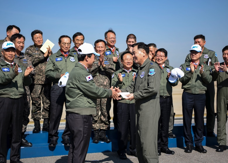 Republic of Korea Air Force Lt. Gen. Lee, Keon Wan, Air Force Operations Command commander, receives a gift from Ahn, Gyubaek, National Defense Committee chairman, at Osan Air Base, ROK, Oct. 25, 2018. Members of Team Osan hosted an aircraft and munitions display for the NDC as part of their ROK AFOC site visit. (U.S. Air Force photo by Airman 1st Class Ilyana A. Escalona)