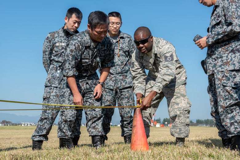 U.S. Air Force Tech. Sgt. Romain Smith, 374th Civil Engineer Squadron electrical power production, works with members of the Koku Jietai (Japan Air Self-Defense Force) members to measure out the proper positioning for the Mobile Aircraft Arresting System (MAAS) at a bilateral training event at Yokota Air Base, Japan, Oct. 25, 2018.