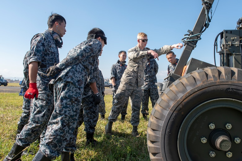 Airman 1st Class Cameron Connelly, 374th Civil Engineer Squadron electrical power production, provides instructions to Koku Jietai (Japan Air Self-Defense Force) service members prior to installing the Mobile Aircraft Arresting System (MAAS) at a bilateral training event at Yokota Air Base, Japan, Oct. 25, 2018.